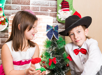 Boy gentleman and girl in ball dress by fireplace
