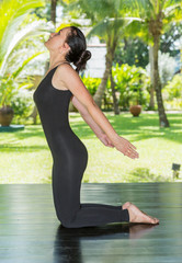 Young woman is practicing yoga and pilates on nature.