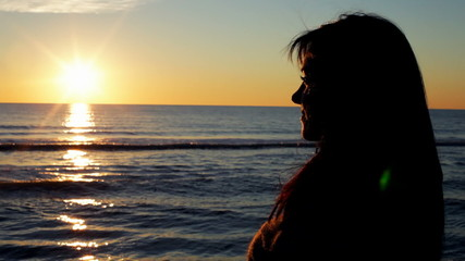Happy woman watching wonderful sunset on beach
