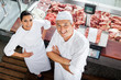 Leinwanddruck Bild - Confident Butchers Standing At Butchery Counter