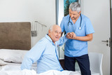Senior Man Being Assisted By Male Caretaker In Bedroom