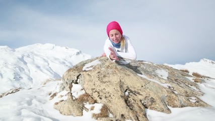 Woman on top of mountain offering helping hand-Climbing