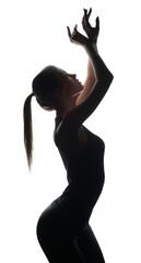 Silhouette of petite dancer posing at camera