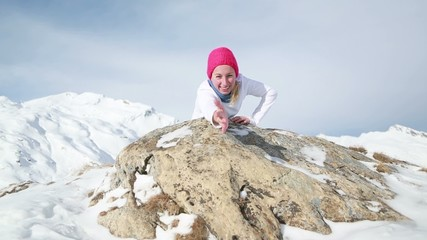 Woman on snow capped mountain offering helping hand