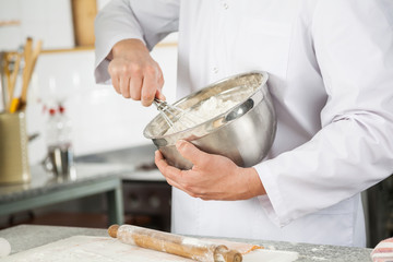 Chef Mixing Batter With Wire Whisk In Bowl In Kitchen