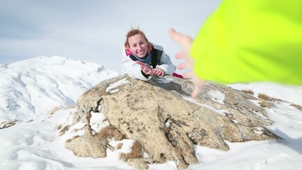 Woman offering helping hand on mountain top-Winter
