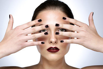Beauty portrait of a young woman showing her manicure