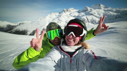 Happy couple taking selfie on ski slopes