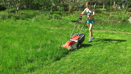 The girl child mowing the lawns. 4K.