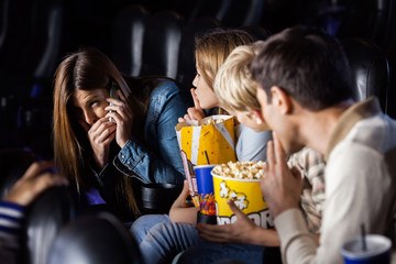 Family Looking At Woman Using Mobilephone In Theater