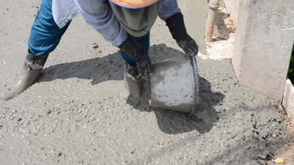 Construction worker finishes pouring concrete floor