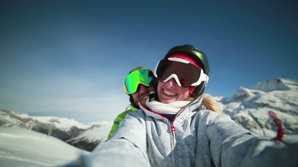 Playful couple on ski slopes taking a selfie