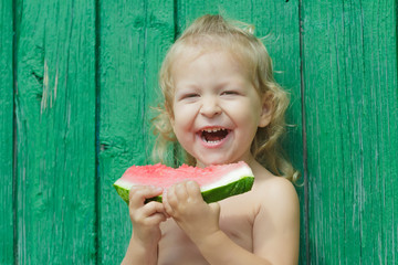 Two-year-girl laughing and holding watermelon