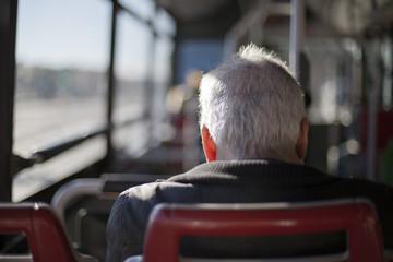 Hombre de pelo cano en asiento de autobús