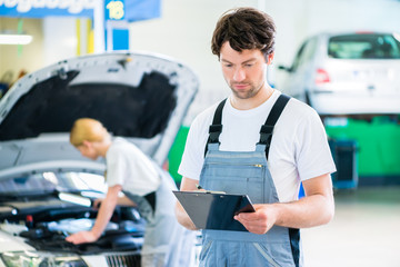 Mechaniker Team arbeitet in Autowerkstatt