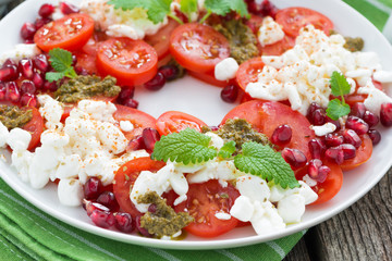 fresh salad with tomatoes, cottage cheese, pesto and pomegranate