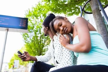 Afrikanischer Pärchen warten an Bushaltestelle