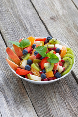 Fruit and berry salad on wooden table, vertical