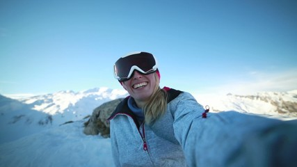 Happy young woman taking selfie on ski vacations