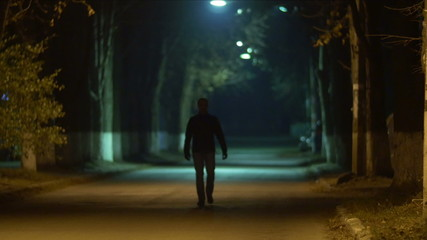 The man walk at the night city street alley with lantern