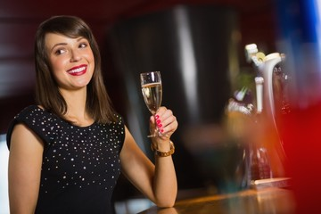 Pretty brunette drinking glass of champagne