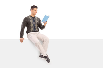 Casual guy reading a book seated on a blank panel