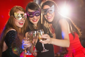 Friends in masquerade masks toasting with champagne