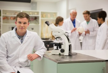Happy medical student working with microscope