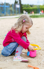 little girl playing in the sand toys