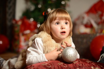 little girl looking up and holding a Christmas ball