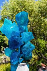 Blue Glass Sculpture in Green Public Garden