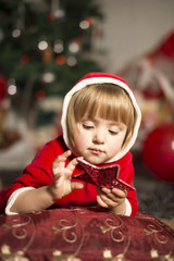 girl in a Santa costume holding and looking at a Christmas star