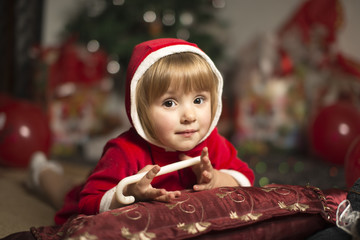 little girl in a Santa costume laying holding a lollipop