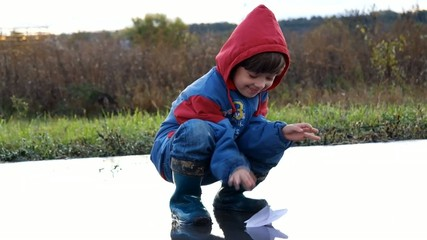 boy playing in puddle with paper ship