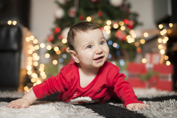 baby on the carpet in front of a Christmas tree laughing