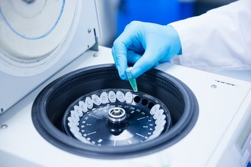 Close up of a chemist using a centrifuge