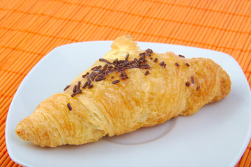 Croissant with chocolate on wooden background. Breakfast.