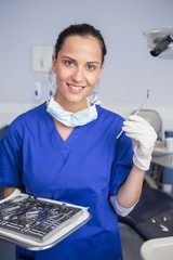 Smiling dentist holding tray and angle mirror