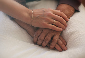 Young hand holding an elderly woman's hand