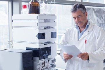 Scientist standing in lab coat reading analysis