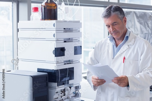 canvas print picture Scientist standing in lab coat reading analysis
