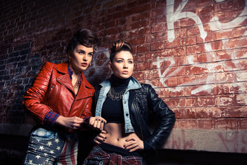 Two pretty women posing near brick wall