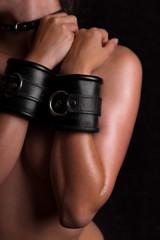 nackte Frau mit ledernen Handschellen