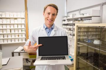 Happy pharmacist showing laptop screen