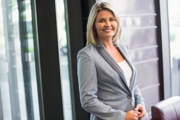 Blonde businesswoman smiling at camera