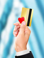 man holding a gold card and a small heart