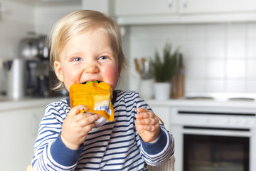 Child smiling with a pack of fruit puree