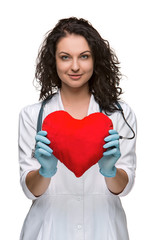 Pretty woman doctor holding a red heart