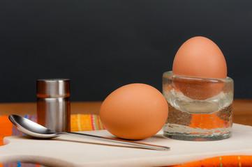 2 Eier auf einem Holzbrett vor dunkelgrauem Hintergrund