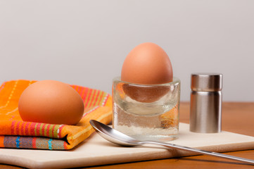 2 Frühstückseier auf einem Holzbrett vor weiß.